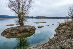 Blick über einen See mit kleiner baumbestandener Insel.