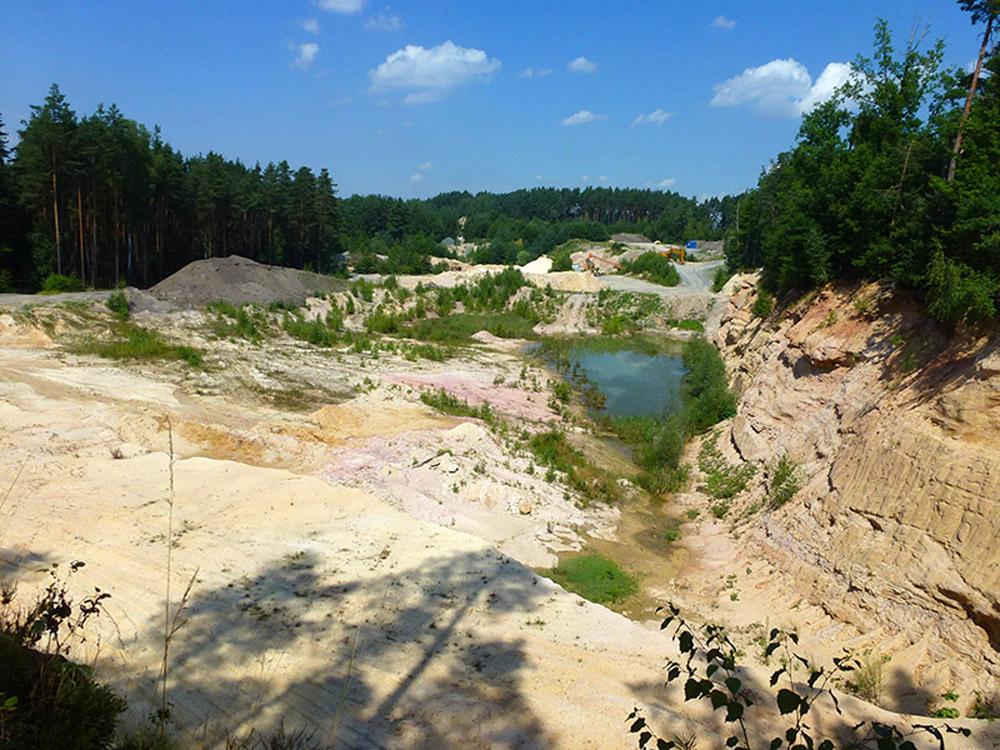 Eine offene Sandgrube mit Sand- und Wasserflächen.