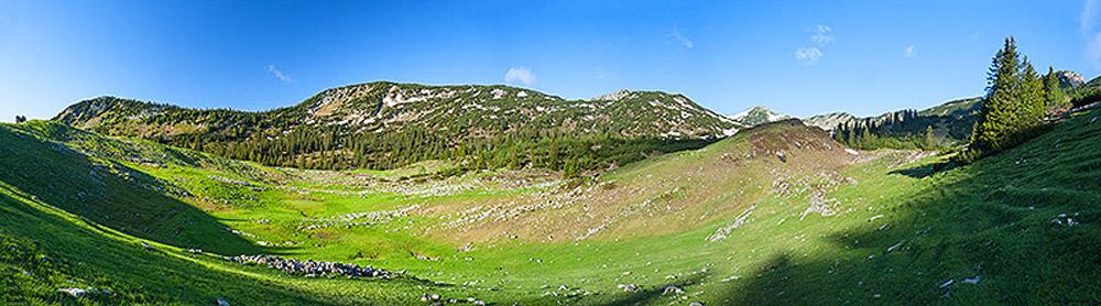 Alpenlandschaft mit Almwiesen vor latschenbewachsenen Hängen.