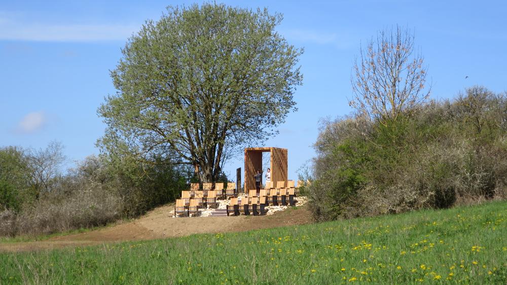 Zwei Dutzend Klappstühle aus Holz stehen in der freien Landschaft und bilden ein Open-Air-Kino der besonderen Art.