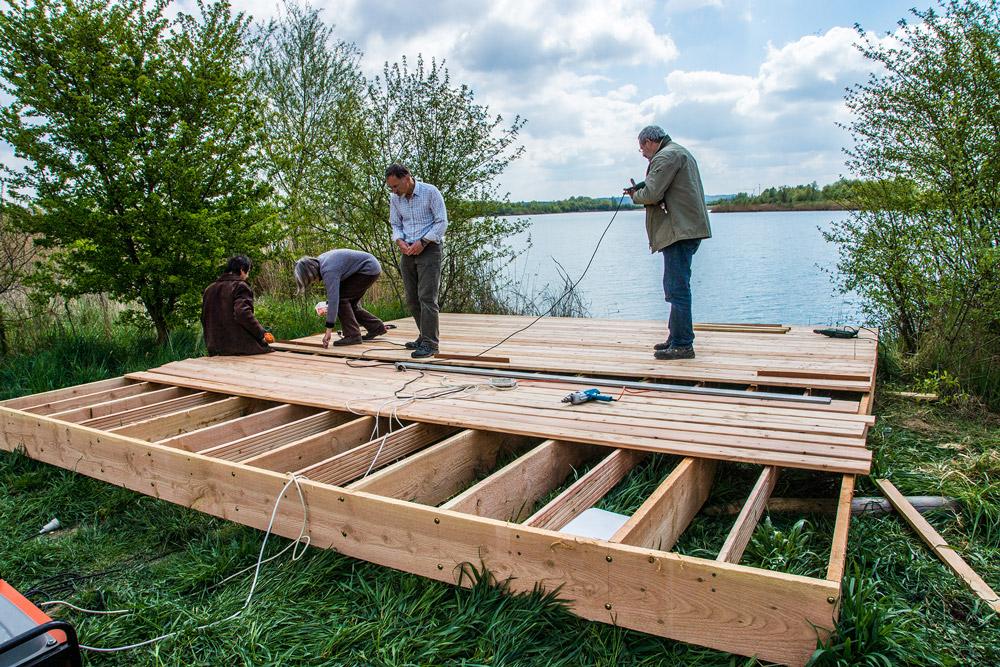 Vier Personen bauen am Ufer eines Sees ein Floß aus Holzbrettern.