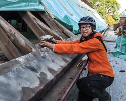 Eine Frau in oranger Jacke und Helm kniet auf einem Hausdach und hält ein Vogelnest in Händen.