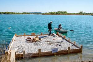 Ein Mann paddelt mit einem Boot zu einem anderen Mann, der auf einem halbfertigen Holzfloß steht.
