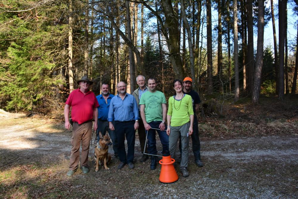 Gruppenfoto mit sechs Männern, einer Frau und einem Schäferhund auf einem Waldweg.