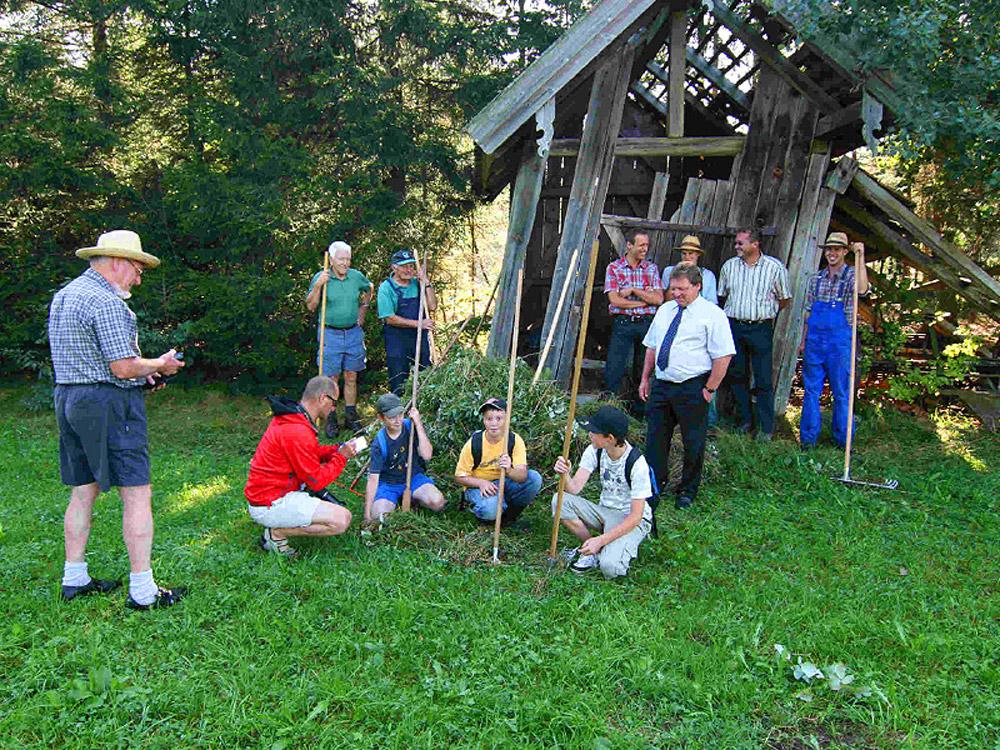 Vor einem Holzschuppen rasten auf einer grünen Wiesen ein Dutzend Männer und Kinder, von denen einige Sensen und Rechen in der Hand halten.