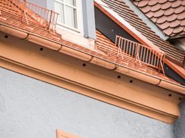 Detailansicht einer frisch renovierten Hausfassade mit Ziegeldach, Schneefang und Dachgauben.