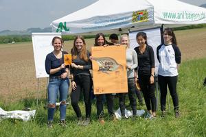 Sechs Schülerinnen stehen im Freien auf einem Feld und halten ein Info-Plakat über das Rebhuhn.