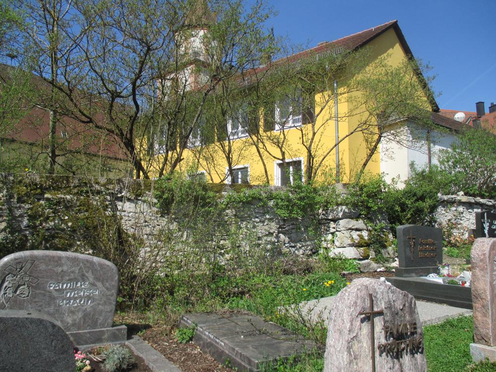 Friedhofsmauer mit Gräbern im Vordergrund und Kirche im Hintergrund.
