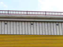 Detailansicht einer modernen Hausfassade mit drei künstlichen Einflugslöchern für Vögel.