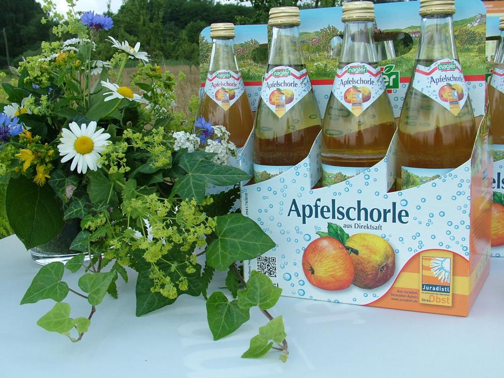 Auf einer weißen Auslage steht neben einem Wildblumenstrauß gefüllte Saftflaschen in einem Karton mit der Aufschrift Apfelschorle aus Direktsaft und Juradistl-Obst.