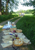 Auf einem Tisch in der freien Landschaft stehen Körbe mit aufgeschnittenem Brot und verschiedene Gläser mit Aufstrich zur Brotzeit für eine im Hintergrund wartende Gruppe von Jugendlichen bereit.