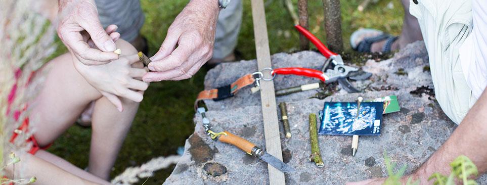 Auf einem großen Stein liegen verschieden Äste und Werkzeuge zum Schnitzen.