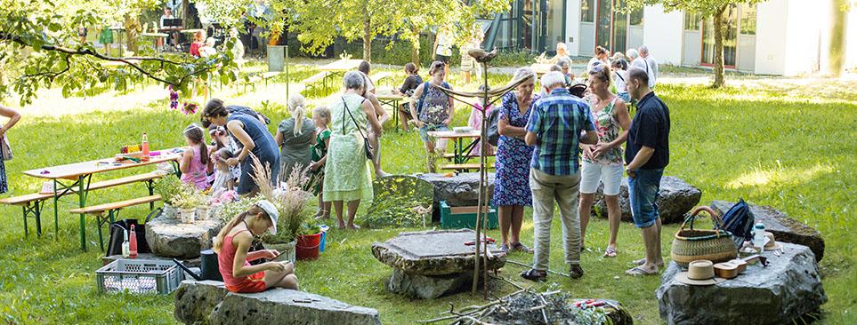 Viele Besucher unterhalten sich im Garten.