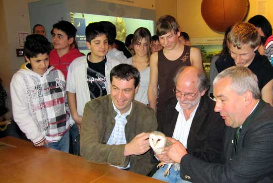 Minister of State, Dr. Markus Söder, Dr. Ludwig Spänle and the teacher Wilhelm Holzer show an owl to the students standing behind them.