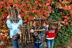 Vier Kinder stehen vor einer herbstlichen mit wildem Wein begrünten Wand und halten sich selbstgemachte Holzflöße vor die Gesichter.