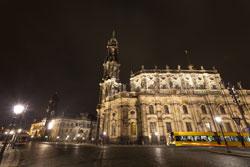 Nachtaufnahme der flächig beleuchteten Dresdner Hofkirche mit Straßenbahn davor.