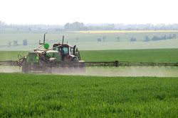 In einer flach welligen Agrarlandschaft sieht man von hinten einen Traktor mit Spritzanhänger, der über die Ausleger ein noch niedrigwüchsiges Getreidefeld einnebelt.