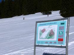 """Informationstafel des DAV über die Kampagne """"Skibergsteigen umweltfreundlich"""", im Hintergrund zwei Skitourengeher beim Aufstieg."""