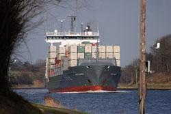 Auf dem Bild ist ein beladenes Containerschiff auf dem Nord-Ostsee-Kanal zu sehen.