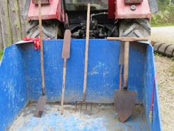 Das Foto zeigt die blaue Ladefläche eines Traktors mit verschiedenen Torfstichwerkzeugen.