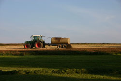 Traktor mit Gülletank auf einer Ackerfläche während der Ausbringung.