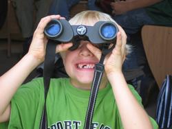 Ein Junge mit Zahnlücken hält ein Fernglas in den Händen und sieht sich etwas aus der Ferne an.