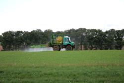 Ein Unimog bringt Pestizide auf einem Feld aus.