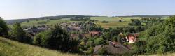 Panoramabild einer Landschaft mit Siedlung, Feldern und Wäldern.