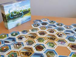 """Das Bild zeigt eine Fläche aus mehreren 6-eckigen Spielelementen, im Hintergrund die aufgestellte Packung des Spieles """"Ecogon – Stille Wasser"""" (Foto: Melanie Schuhböck)."""