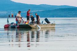 Fünf Personen stehen auf zwei nebeneinanderliegenden Booten auf einem See. Im Hintergrund bewaldete Hügel.